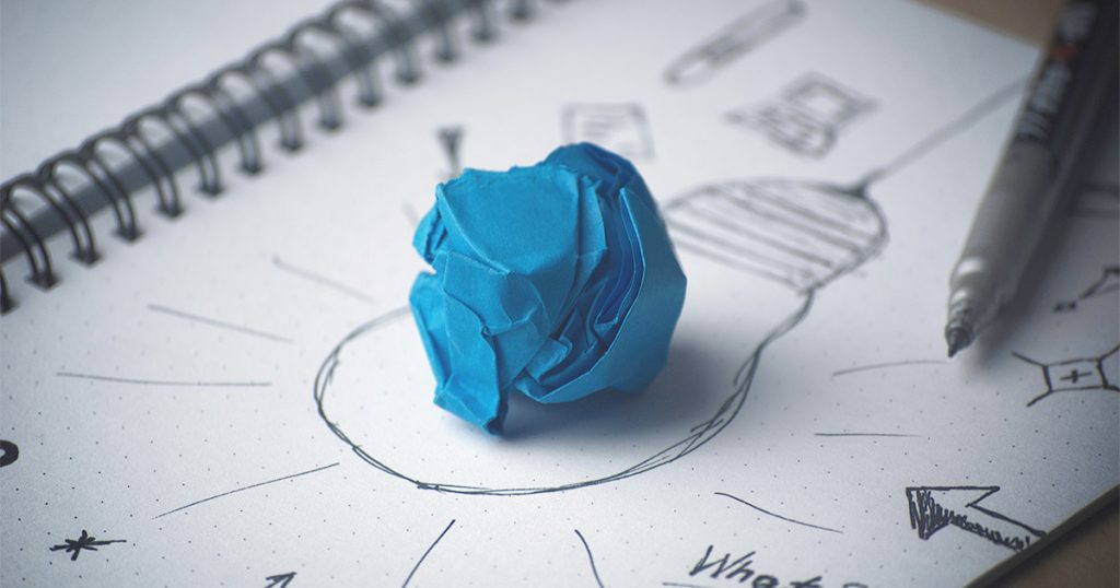 Na imagem, uma folha de papel com vários desenhos. Ao centro da folha existe o desenho de uma lâmpada e em cima do caderno, uma folha azul amassada.
