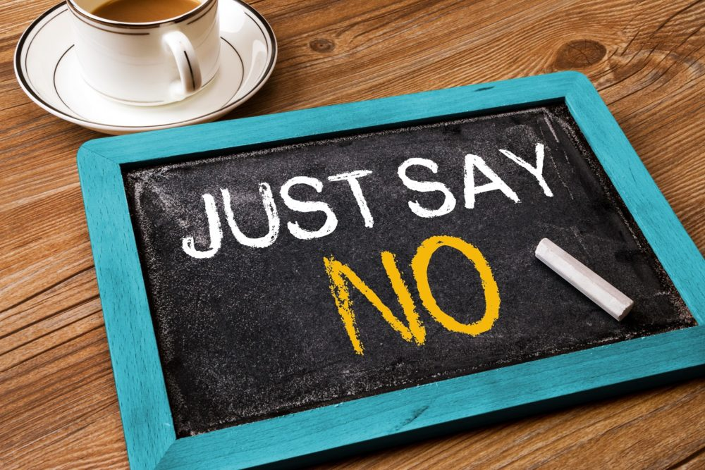 """Na imagem existe uma mesa de madeira com um quadro escrito em inglês: """"Just Say No"""" (Apenas diga não). Ao lado do quadro existe uma xícara de café."""