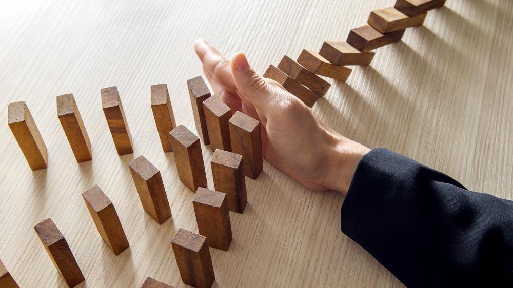 Na imagem a mão de uma pessoa interrompe a queda de vários pequenos blocos de madeira quadrados