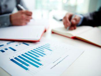 imagem com papeis e gráficos de um relatório